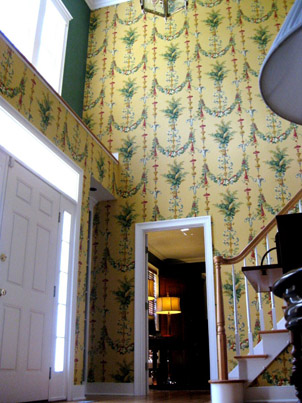 A large open foyer is warmed by a beautiful large repeat hand-printed French wallpaper.
